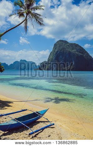 An boat under Palms on Tropical island, Big Rock Depeldet island on background, cloudy sky El Nido, Palawan, Philippines, Asia