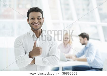 Cheerful team leader. Handsome young African man showing ok and smiling while two people working on background