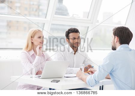 They are coming up with another great idea. Group of cheerful business people sitting together at table and discussing something