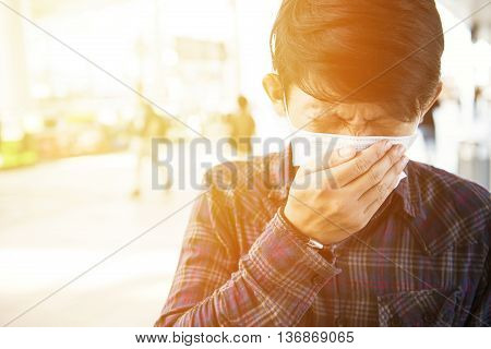 young asian man feeling unwell at outdoor