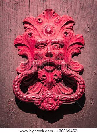 Red door knocker of an old door.