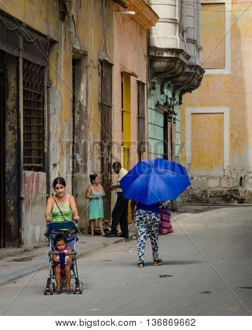 HAVANA - CUBA JUNE 19, 2016: Street scene with woman pushing her baby in a stroller in the historic La Habana Vieja neighborhood.