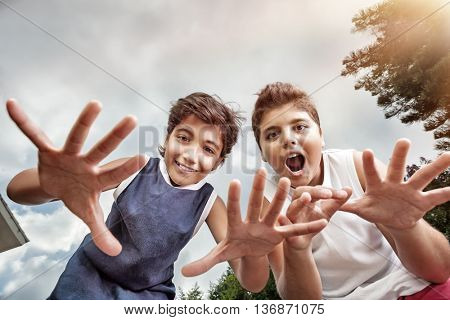Two happy boys having fun outdoors, making faces to the camera, best friends enjoying holidays in a summer camp