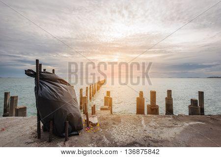 Black garbage bag on concrete floor at ocean in sunset, vintage tone