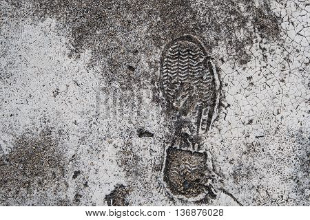 Foot print on grunge concrete texture background