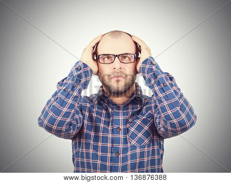 Man With Glasses Holding His Head With His Hands.