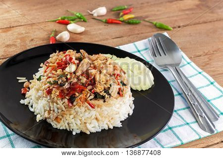 Rice topped with stir fried crab meat and basil in black dish on white wood