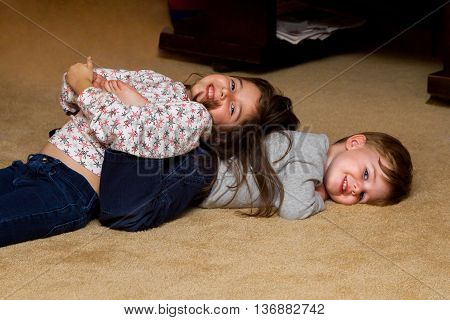 Siblings playing on floor. The older sister is laying on the younger brother's back and both are grinning at the camera.