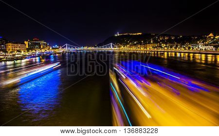 Cruise Boats Danube River Passing Under Chain Bridge Night Budapest Hungary. Elizabeth Bridge in the distance