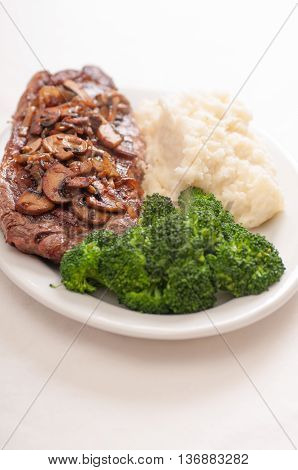 medium rare sirloin strip setak with creamy mashed potatoes and broccoli