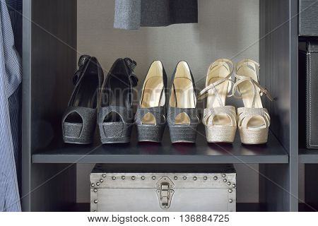 Row Of Women's Shoes On Black Wooden Shelf