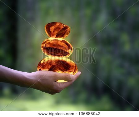 Pyramid of the stones of fire on a female hand. Natural green background. Concept - calm stability ecology environmental protection