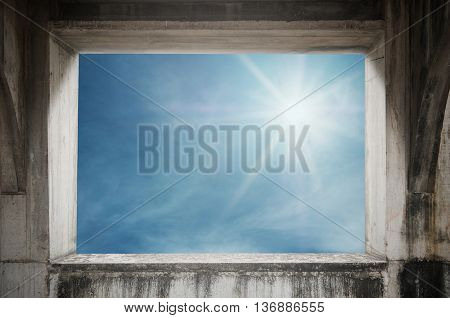 Old concrete window frame with skyscape view and bright sunlight