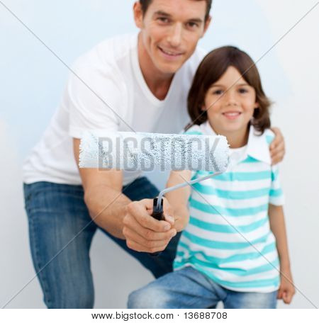 Happy father and his son holding a paintbrush