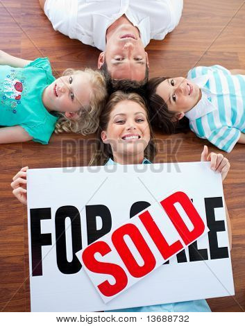 Happy family celebrating buying their new house lying on the floor