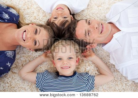 Smiling young family lying on the floor with heads together