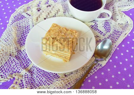 Cake of puff pastry and sweet custard. Piece of cake on the plate, coffee Cup, spoon. A delicious dessert