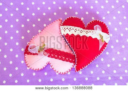 Two felt hearts. Red and pink felt hearts with lace and little metallic key on purple background. Valentine's day gift, wedding gift