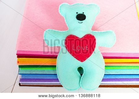 Blue felt bear with red heart and the words Love. Soft wool toy for children. Set of colored felt sheets