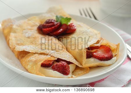 Thin crepes with cheese filling and dusted with icing sugar