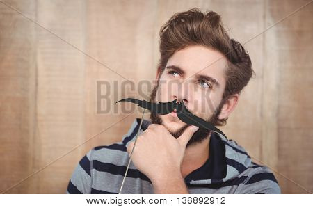 Close-up of thoughtful hipster with hand on chin against artificial mustache