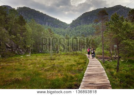 FORSAND, NORWAY - JULY 12, 2015: Unidentified group of tourists on hiking trail to Preikestolen (Pulpit Rock) a famous tourist attraction in Norway.