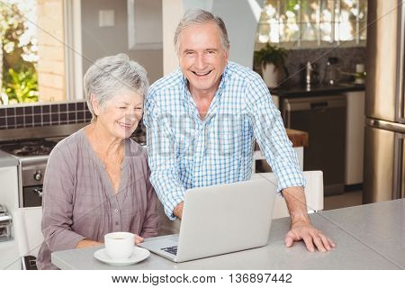 Happy senior man standing besides wife with laptop in kitchen at home