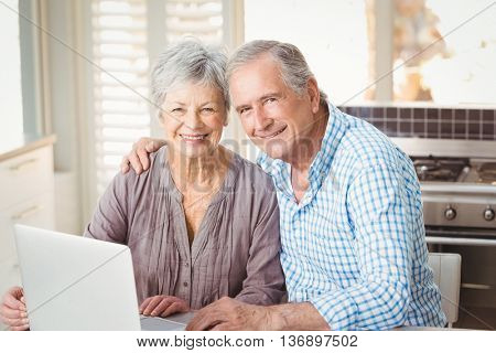 Portrait of happy senior couple with laptop while sitting in kitchen