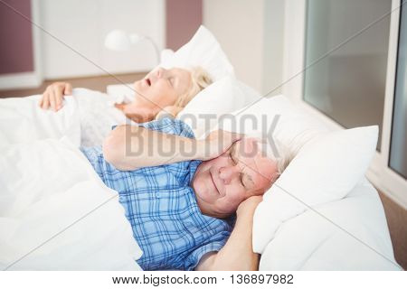 Disturbed man covering ears from snoring wife while sleeping on bed