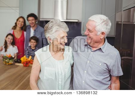 Happy grandparents standing with family in kitchen at home