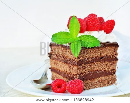 Piece of chocolate cake with whipped cream icing and fresh raspberry on white plate