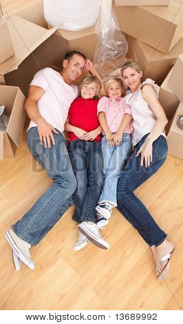 Smiling family lying on the floor while moving house