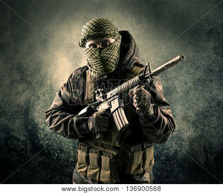 Portrait of a heavily armed masked soldier with grungy background concept