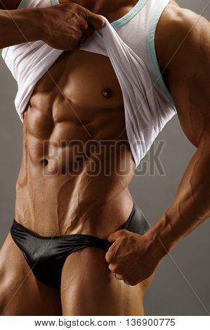 Strong athletic torso man on gray background