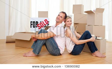 Smiling couple relaxing sitting on the floor while moving