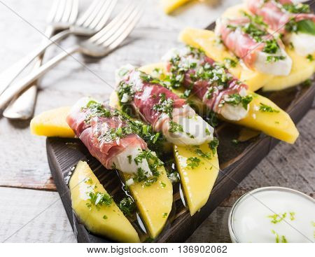Rolls of mozzarella, basil and Parma ham on slices of mango with yoghurt sauce on wooden cutting board. Healthy eating concept.