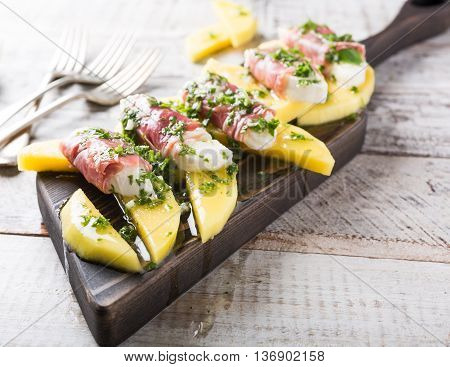 Rolls of mozzarella, basil and Parma ham on slices of mango with yoghurt sauce on wooden cutting board. Healthy eating concept with copy space