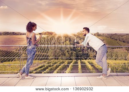 Young Couple Toasting In A Vineyard At Sunrise