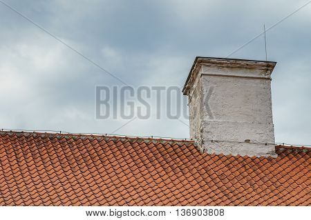 Tiled roof and chimney with lightning rod against cloudy and stormy sky