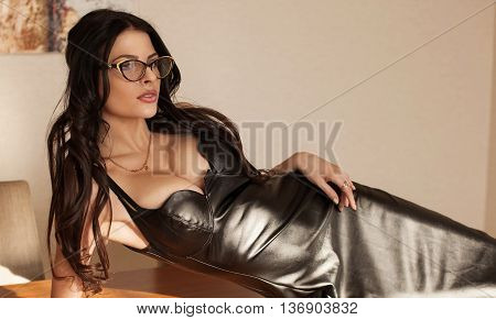 Beautiful sexy brunette young woman wearing black leather short dress sitting on table. Fashionable female with attractive body posing provocatively, indoor. Sensual girl with big boobs.
