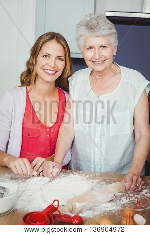 Portrait of smiling mother and daughter preparing food in kitchen at home