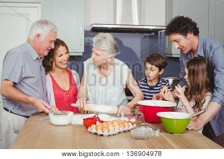Happy family cooking food on table in kitchen at home
