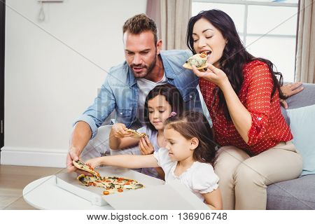 Family of four eating pizza while sitting on sofa at home