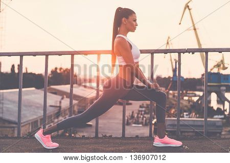 Woman stretching. Full length side view of beautiful young woman in sports clothing doing stretching exercises while standing on the bridge with evening sunlight and urban view in the background