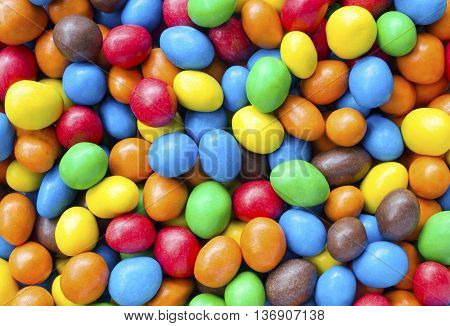 Close up of a of a pile of multicolour coated sweets from overhead