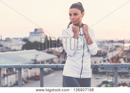 Sports style. Beautiful young woman adjusting her sports clothes and looking away while standing on the bridge