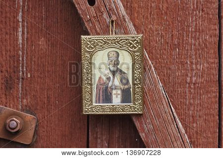 Saint Nicholas icon on red painted board wall