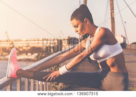 Stretching before jogging. Beautiful young woman in sports clothing doing stretching exercises while standing on the bridge