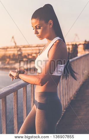 Smart helper. Beautiful young woman in sports clothing looking at her smartwatch while standing on the bridge