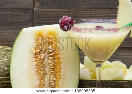melon drink in stemware with slice of melon